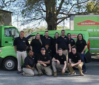 Photo of the crew in front of our green trucks