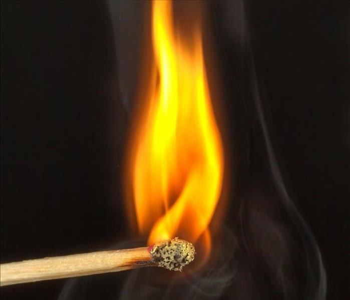 A lit match with flame and smoke rising from tip
