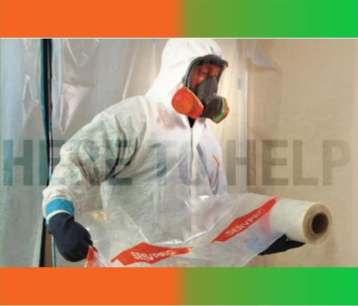 SERVPRO technician in protective gear cleaning